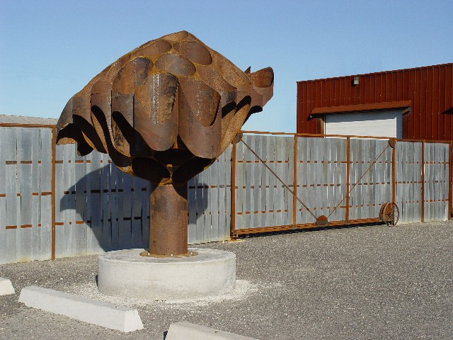 """""""A Miner's Memorial"""", 10 feet tall by 10.5 feet in diameter, """"Artifact Steel"""", 2003 ■    """"A Miner's Memorial"""" was formed from 160 feet of salvaged 20 inch diameter riveted water pipe. This pipe was manufactured by rolling 4 foot long pieces of sheet steel into pipe and fastening the overlapping joint with rivets. Five of the 4 foot lengths were riveted end to end to form 20 foot long pieces that were then joined in the field to form water pipelines. ■"""