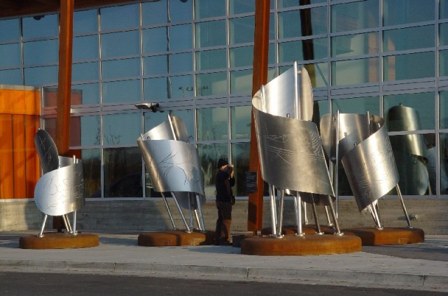 """Migration"", a group of 5 figures measuring 20 feet by 28 feet by 11 feet tall, stainless steel on mild steel structural bases, 2006-2008 ■    'Migration' is a 'Percent for Art' commission for a new Fairbanks International Airport Terminal. Located adjacent to the departure entrance, it is a migrating group of five stainless steel figures eight to eleven feet tall. The exposed outside surface of each figure displays etched migration imagery by Alaskan Native artist Ron Senungetuk. Fabricated in Fairbanks, it was installed in September 2008. ■"