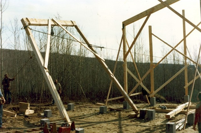 """The timber frame structure was first wrapped from the outside with horizontal 1x4, @ 16"""" o.c. This was backing on the inside for vapor barrier and curved 5/8"""" gypsum board finish. Then from the outside, vertical 12"""" truss joist, @ 48"""" o.c. were fastened to these 1x4's. Then outside of and fastened to the truss joist were a double layer of 1x4 horizontal @ 24"""" o.c. as backing for the vertical exterior white spruce channel siding on 30# felt. So a timber frame with a truss joist curtain wall. The truss joist insulation cavity had 2 staggered horizontal layers of 6""""x24"""" fiberglass. ■"""